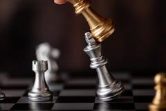 拿着在比赛的手金国王攻击银色领导 免版税图库摄影