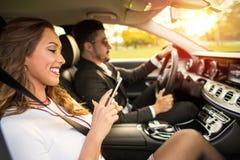 拿着在汽车的美丽的女实业家一个智能手机 免版税图库摄影