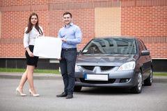 拿着在汽车的背景的年轻夫妇白色板料 免版税库存图片