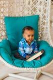 拿着在沙发的非裔美国人的男婴画象书 免版税库存图片