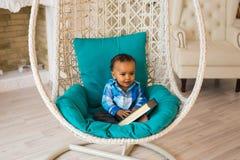 拿着在沙发的非裔美国人的男婴画象书 免版税图库摄影