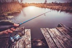 拿着在河的人实心挑料铁杆 捕鱼 免版税库存图片