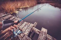 拿着在河的人实心挑料铁杆 捕鱼 免版税图库摄影