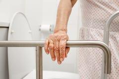 拿着在洗手间的年长妇女扶手栏杆 库存照片