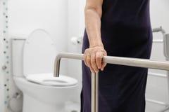 拿着在洗手间的年长妇女扶手栏杆 免版税图库摄影