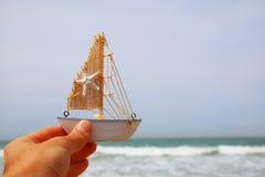 拿着在海天线前面的人的手一条小船 库存照片