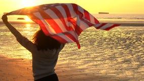 拿着在海滩的女孩少年女性少妇美国美国星条旗旗子在日落或日出 股票视频