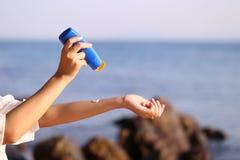 拿着在海滩的妇女手遮光剂与海在天空蔚蓝背景、spf sunblock保护和皮肤护理概念中 免版税库存照片