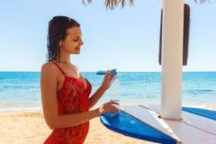 拿着在海滩的愉快的少妇水 opeining水瓶的一个愉快的女孩的画象户外在海滩 免版税库存图片