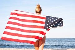 拿着在海滩的美丽的爱国的妇女一面美国国旗 美国独立日,7月4日 自由概念 免版税库存照片