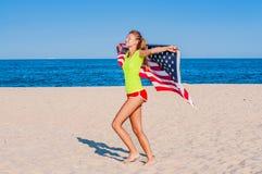 拿着在海滩的美丽的爱国的快乐的妇女一面美国国旗 免版税图库摄影