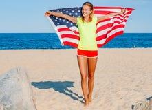 拿着在海滩的美丽的爱国的快乐的妇女一面美国国旗 库存图片
