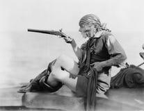 拿着在海盗成套装备的一个少妇的档案一个燧发枪雌蕊(所有人被描述不是更长生存和没有庄园 免版税图库摄影