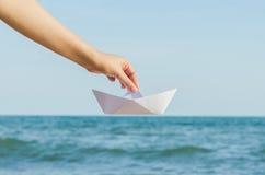 拿着在海背景的女性手纸小船 库存照片