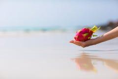 拿着在海背景的女性手龙果子 免版税库存图片