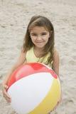 拿着在海滩微笑的女孩画象beachball 库存照片