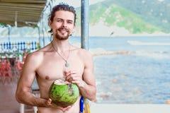 拿着在海滩的一个可爱的年轻人一个绿色椰子 免版税库存照片