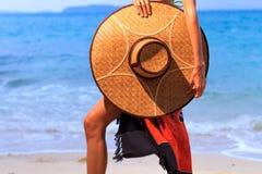 拿着在海滩的亚洲设计一个帽子 免版税图库摄影