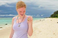 拿着在海滩的十几岁的女孩一个螃蟹 免版税库存照片