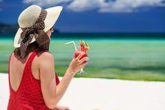 拿着在海滩的少妇西瓜鸡尾酒 免版税库存图片