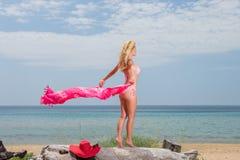 拿着在海滩的红色比基尼泳装的少妇布裙 免版税图库摄影