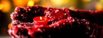 拿着在温暖的手套的妇女圣诞节candel 免版税图库摄影
