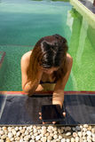 拿着在游泳池的亚裔妇女数字式片剂 库存图片