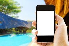 拿着在游泳池背景的手电话 免版税库存照片