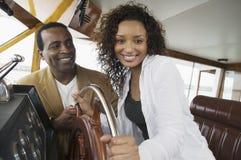 拿着在游艇的夫妇方向盘 免版税库存图片