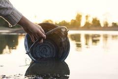 拿着在湖的妇女的特写镜头手一个桶 库存图片