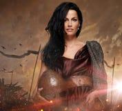 拿着在火的可爱的战争女王/王后盔甲发火花 库存图片
