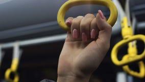 拿着在火车或地铁,在公共交通工具的毒菌的女性手扶手栏杆 影视素材