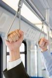 拿着在火车的人们把柄 库存图片