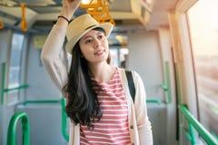 拿着在火车里面的妇女扶手栏杆 免版税库存照片