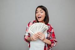 拿着在灰色墙壁的情感妇女金钱 免版税库存照片