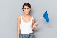拿着在灰色的爱国的微笑的妇女欧洲旗子 免版税库存图片