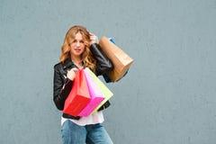 拿着在灰色背景的愉快的俏丽的女孩购物带来 消费者至上主义、购物、销售和生活方式概念 伟大季节性 免版税库存图片