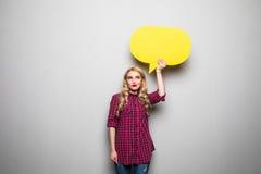 拿着在灰色背景的美丽的白肤金发的少妇黄色空白的讲话泡影 库存照片