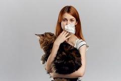 拿着在灰色背景的年轻美丽的妇女一只猫,过敏对宠物 图库摄影