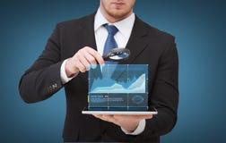 拿着在片剂个人计算机的商人手放大器 免版税库存照片
