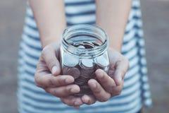 拿着在玻璃瓶的少妇硬币在手上 免版税库存照片