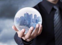 拿着在球形里面的商人一个城市 图库摄影