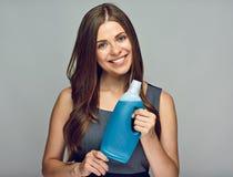 拿着在瓶的微笑的妇女更加干净的产品 工作室 库存照片