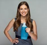 拿着在瓶的微笑的妇女更加干净的产品 免版税库存照片