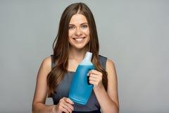 拿着在瓶的微笑的妇女更加干净的产品 免版税库存图片