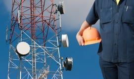 拿着在电信塔的工程师橙色盔甲 免版税库存图片