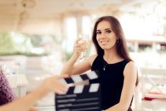 拿着在电影场面的愉快的女演员一块玻璃 库存图片