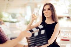 拿着在电影场面的愉快的女演员一块玻璃 库存照片