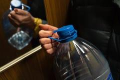 拿着在电梯的更老的资深妇女的手一个大蓝色塑料瓶 库存照片