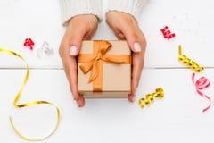 拿着在白色木桌上的女性手一个礼物盒 免版税库存图片
